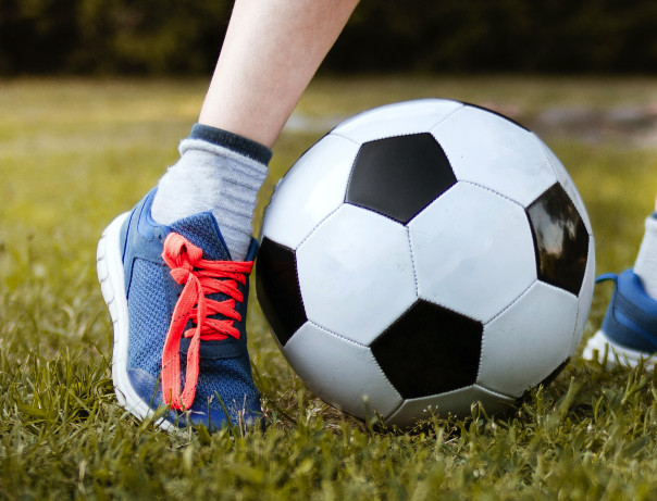 Person playing with a soccer football.